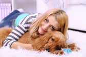 Beautiful young woman with cocker spaniel in room — ストック写真