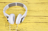 White headphones on wooden table close-up — Stockfoto