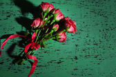Beautiful small pink roses, on blue wooden table — Stock Photo