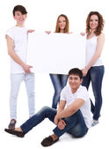 Group of happy young people holding blank poster isolated on white — Zdjęcie stockowe