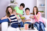 Group of young friends watching television at home — 图库照片