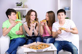 Group of young friends eating pizza in living-room on sofa — Foto Stock