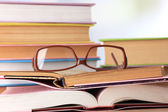 Composition with glasses and books, on table, on light background — Stock Photo