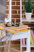Composition with glasses and books, on chair, on cabinet and wall background — Stock Photo