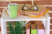 Composition with glasses and books, on cabinet, on color wall background — ストック写真