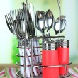 Kitchen cutlery in metal stand on wooden table on bright background — Stock Photo