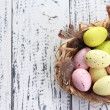 Easter eggs in nest and decorative feathers on color wooden background — Stock Photo #43866457