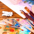 Artistic equipment: paint, brushes and art palette on wooden table — Stock Photo #43868441