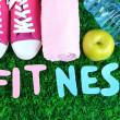 Fitness and healthy life. Conceptual photo. Gumshoes, towel, dumbbells and water bottle on green grass background — Stock Photo #43869899