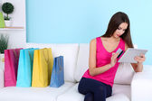 Beautiful young woman holding tablet with shopping bags on sofa on blue background — Foto de Stock