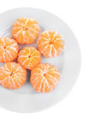 Ripe sweet tangerines on color plate, isolated on white — Stock Photo