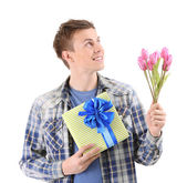Portrait of handsome young man with flowers and gift, isolated on white — Stok fotoğraf