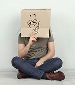 Man with cardboard box on his head sitting on floor near wall — Stock Photo