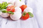 Tasty mozzarella cheese with basil and tomatoes, on wooden table — Foto Stock