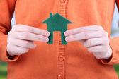 手のクローズ アップ、明るい背景に小さな紙の家 — ストック写真
