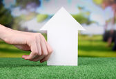 Little paper house in hand close-up, on green grass, on bright background — ストック写真