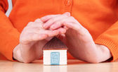 Little paper house in hand close-up, on light background — Stockfoto