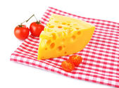 Piece of cheese and tomatoes,on color napkin, isolated on white — Stockfoto