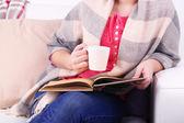 Kobieta siedzi na kanapie, czytanie książki i picia kawy lub herbaty, szczelnie-do góry — Zdjęcie stockowe