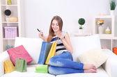 Jovem mulher sentada com sofá e segurando o cartão de crédito na mão, em casa — Fotografia Stock
