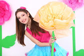 Beautiful young woman in petty skirt holding big flower on decorative background — Stock fotografie