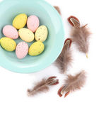 Easter eggs in bowl and decorative feathers isolated on white — Stock Photo
