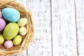 Huevos de pascua en el nido en el fondo de madera color — Foto de Stock