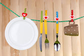 Tableware dried on rope on wooden background — Stock Photo