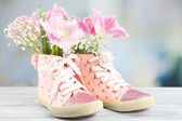 Beautiful gumshoes with flowers inside on wooden table, on bright background — Stock fotografie