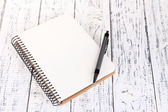 Notebook with pen on color wooden background — Stock Photo