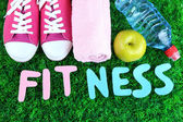 Fitness and healthy life. Conceptual photo. Gumshoes, towel, dumbbells and water bottle on green grass background — Stock Photo