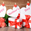 Happy Mothers Day message written on paper hearts with flowers on brown background — Stock Photo