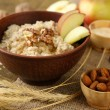 Tasty oatmeal with nuts and apples on wooden table — Stock Photo #43878117