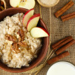 Tasty oatmeal with nuts and apples on table close up — Stock Photo #43878137