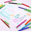 Kids drawing of family and colored pencils on wooden table — Stock Photo #43878651