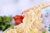 Tasty instant noodles with vegetables in bowl on table on light background — Stock Photo