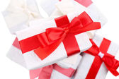 Beautiful gifts with red ribbons, close up — Stock Photo