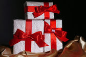 Krásné dárky s červené stužky, na tmavém pozadí — Stock fotografie