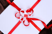 Beautiful gift with red ribbons, close up — Stock Photo