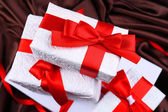 Beautiful gifts with red ribbons on silk background — Photo