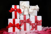 Beautiful gifts with red ribbons on dark background — Stock Photo