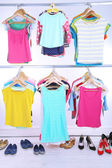 Different clothes on hangers and shoes on light background — 图库照片