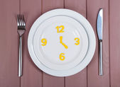 Plate with clock on wooden table close-up — Stock Photo
