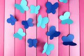 Paper cut out butterflies, on wooden background — Stock Photo