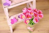 Composition with bouquet of tulips in vase, on ladder, on wall background — Stock Photo