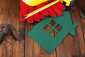 House of felt with helmet and gloves on wooden background — ストック写真