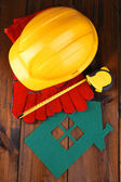House of felt with helmet and gloves on wooden background — Stockfoto