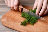 Chopped dill on wooden board close-up — Stock Photo