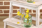 Beautiful Forsythia blossom in transparent jars on brick wall background — Stock Photo