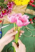 Female hands composing beautiful bouquet, close-up. Florist at work. Conceptual photo — Stock Photo